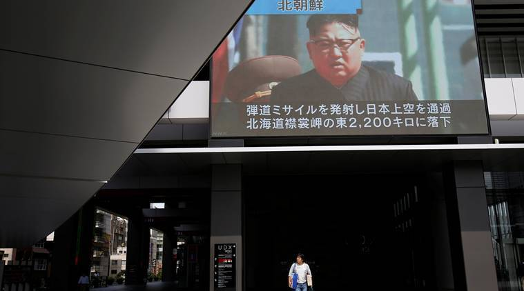 A passerby walks under a TV screen reporting news about North Korea's missile launch in Tokyo Japan