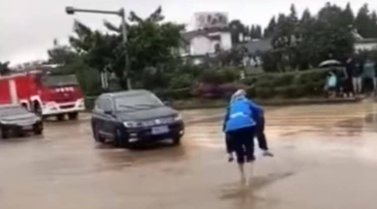 elderly man, old man, man carries wife on back, man carries wife, flooded streets, man carries wife china, china videos, love videos, indian express, indian express news