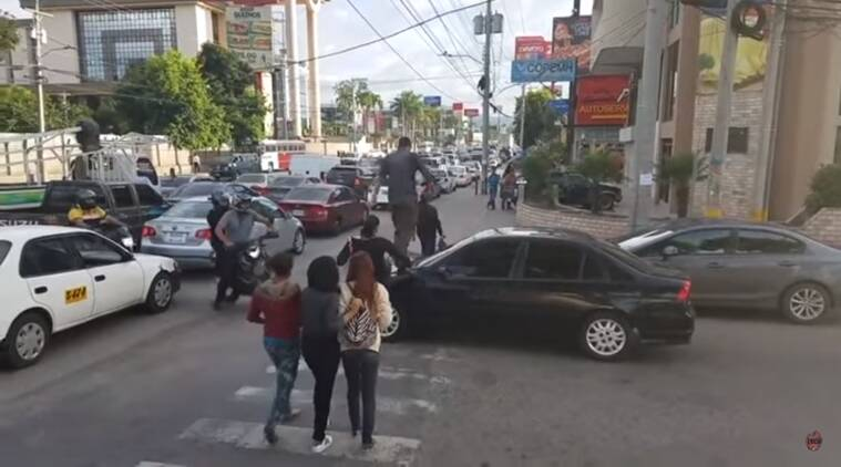 pedestrians walk over car bonnet, pedestrians walking over car, people walk over car, driver parks over zebra crossing, Viral video, traffic rules, Indian express, Indian express news