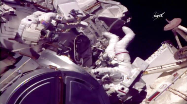 International Space Station astronauts replacing blurry camera on roboticarm