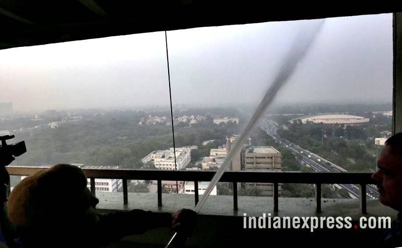 delhi pollution photos, ito water spray photos, water sprayed from building at ito pics, ito water sprinkled pictures, indian express