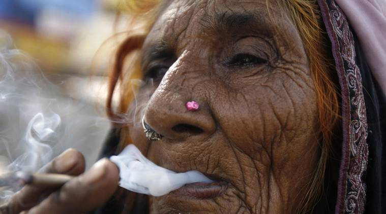 a woman is framed smoking beedi