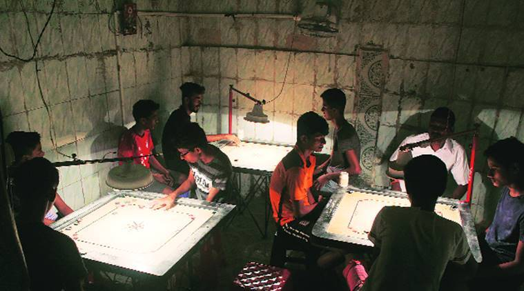 Common cause: In slum lanes, young & old relax over carrom