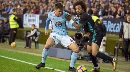 Real Madrid's Marcelo tussles for the ball with Celta Vigo's Radoja