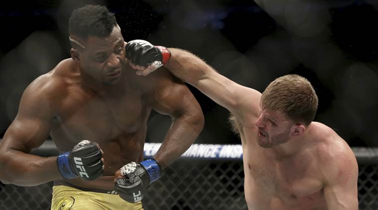 Stipe Miocic lands a right hand against Francis Ngannou during a heavyweight championship mixed martial arts bout at UFC 220