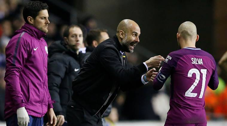 Manchester City manager Pep Guardiola talks with David Silva