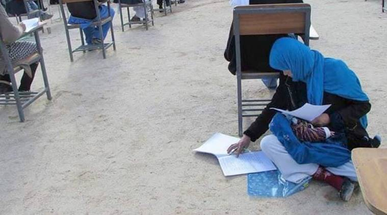Afghanistan woman writing exam with a baby, Afghanistan woman writing exam, Afghanistan woman viral picture