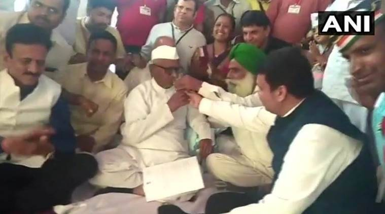 Maharashtra Cheif Minister Devendra Fadnavis offers water to Anna Hazare in Ramlila Maidan, New Delhi, on Thursday. (Photo: ANI)