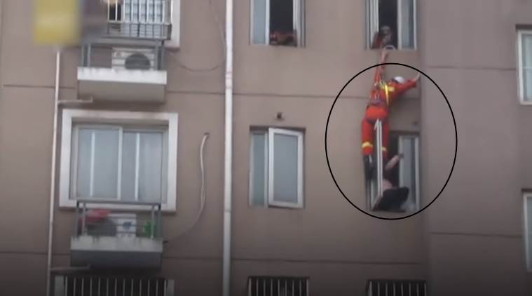 viral video, woman committing suicide, woman saved by firefighter, woman saved in china by being kicked, firefighter saves woman by kicking, indian express, indian express news