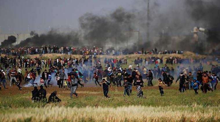 Teargas canisters fired by Israeli troops falls down at Palestinians during a demonstration near the Gaza Strip border with Israel on Friday. (AP photo)