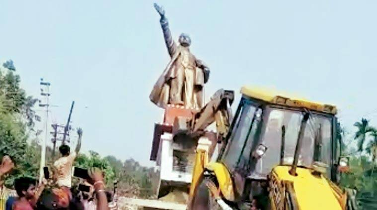 Statue of Lenin being pulled down by some people with an excavator machine in Tripura