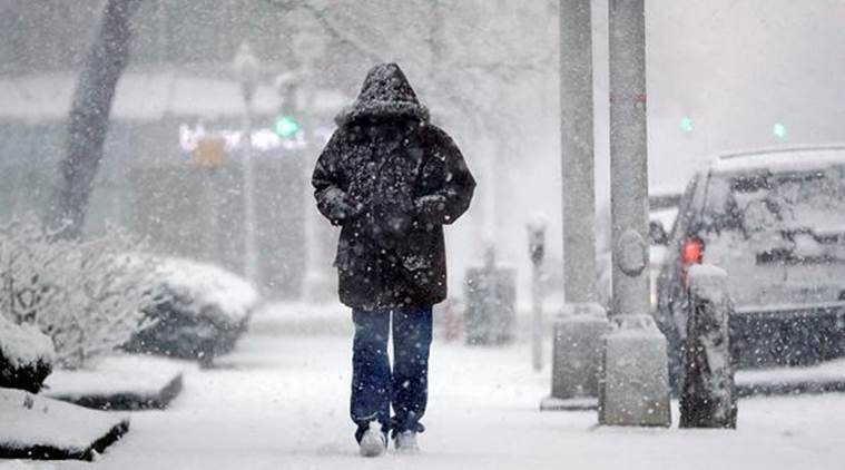 A man walks under light snow at the beginning of a snowstorm in Morristown. (Photo: AP)