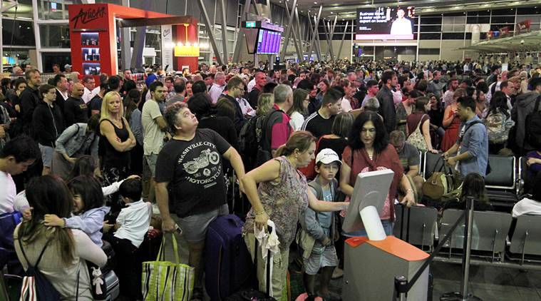 Passengers are seen waiting in line due to hardware and technical issues at the Domestic Airport in Sydney