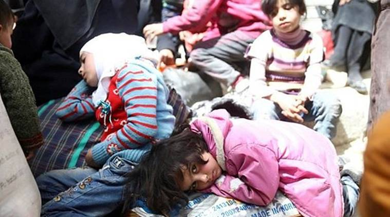 A girl looks at the camera during evacuations from the besieged town of Douma, Eastern Ghouta. (Reuters)