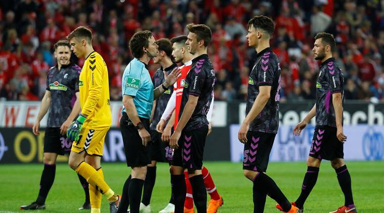 Freiburg's Janik Haberer speaks with referee Guido Winkmann after a penalty is awarded to Mainz