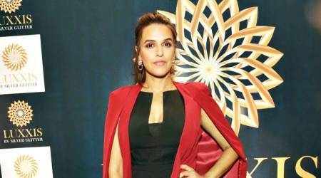 Neha Dhupia adds a pop of colour to her all-black formal outfit and she does it well