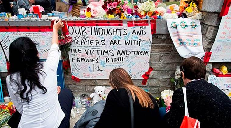 People read and pay tribute at a memorial along Yonge Street, in Toronto, the day after a driver drove a van down sidewalks, striking and killing numerous pedestrians in his path. (AP)