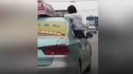VIDEO: Chinese schoolgirl does homework on the roof of a car and it's really scary
