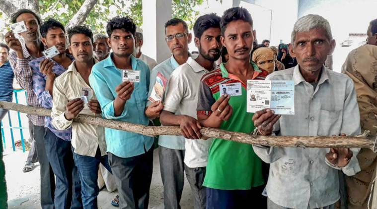 Kairana Bypoll Results 2018 highlights: People stand in a queue to cast their vote during Kairana parliamentary constituency re-polls, at a polling station, in Shamli on Wednesday. (Source: PTI Photo)