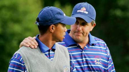 US golfer Phil Mickelson puts his arm around partner Tiger Woods as they walk off the 18th green after they lost to Europeans Darren Clarke and Lee Westwood on the final hole of their foursomes match at the 35th Ryder Cup at Oakland Hills Country Club in Bloomfield Township.