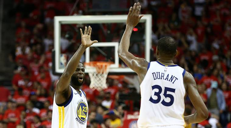 Golden State Warriors forward Draymond Green (23) and forward Kevin Durant (35) high-five in the final seconds of the forth quarter against the Houston Rockets in game seven of the Western conference finals of the 2018 NBA Playoffs