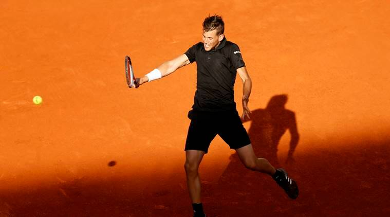 Dominic Thiem hits a backhand return to Rafael Nadal during a Madrid Open tennis tournament match in Madrid, Spain