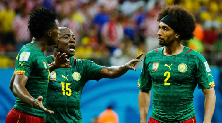 Cameroon's Achille Weboc (C) tries to separate teammates Benjamin Moukandjo (L) and Benoit Assou-Ekotto as they argue during their 2014 World Cup Group A soccer match against Croatia at the Amazonia arena in Manaus