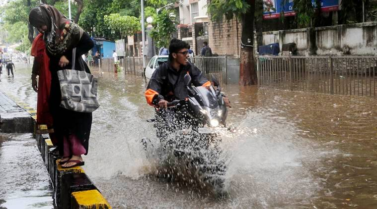 A man splashes water as he rides his bike past a waterlogged street in Mumbai on Thursday. (AP)