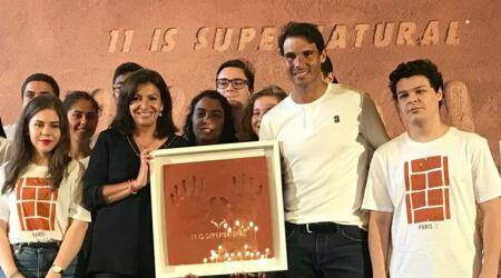 Paris Mayor Anne Hidalgo, left, presents Rafael Nadal, right, with framed handprints bearing 11 fingers in a nod to the 11th French Open titles he won, during a ceremony held at the Paris city hall