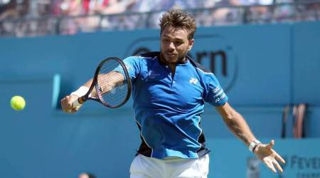 Switzerland's Stan Wawrinka returns a shot during his match against Britain's Cameron Norrie on day one of the Queen's Club Championship at the Queens Club, in London