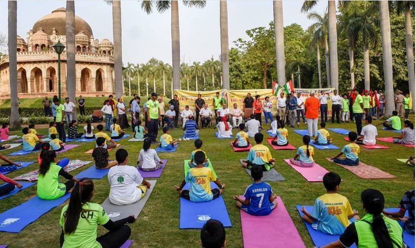 With mask on face thousands join PM Modi for world yoga celebration