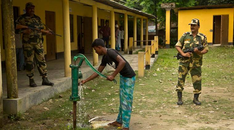 Security men stand guard as Muslim man uses hand pump to drink water after arriving to check if his name is included in the NRC draft in Bur Gaon village, 70 kilometers (44 miles) east of Guwahati, on Monday. (AP)