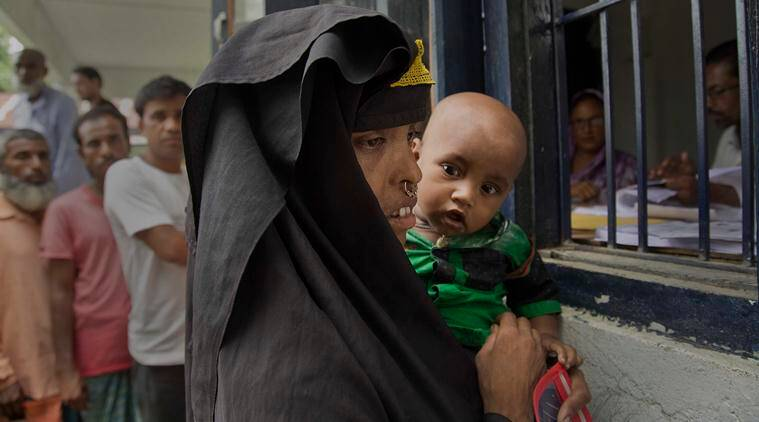 A Muslim woman holding her child checks if their names are included in the NRC list, in Mayoung, about 55 kilometers (34 miles) east of Guwahati, on Monday. (PTI)