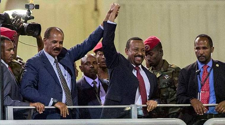 Eritrean President Isaias Afwerki (second left) and Ethiopia's Prime Minister Abiy Ahmed (centre) hold hands as they wave at the crowds in Addis Ababa, Ethiopia on Sunday. (AP)