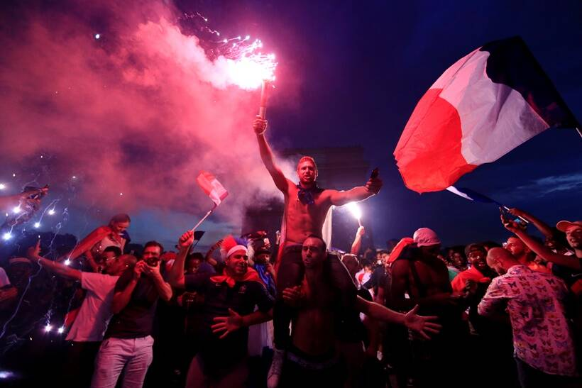 France fans celebrate in front of the Arc de Triomphe on the Champs-Elysees Avenue after France won the Soccer World Cup final.