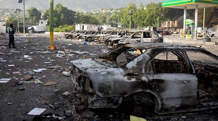 Burned cars sit parked outside the Delimart supermarket complex, near a gas station, after two days of protests against a planned hike in fuel prices in Port-au-Prince, Haiti on Sunday. (AP)