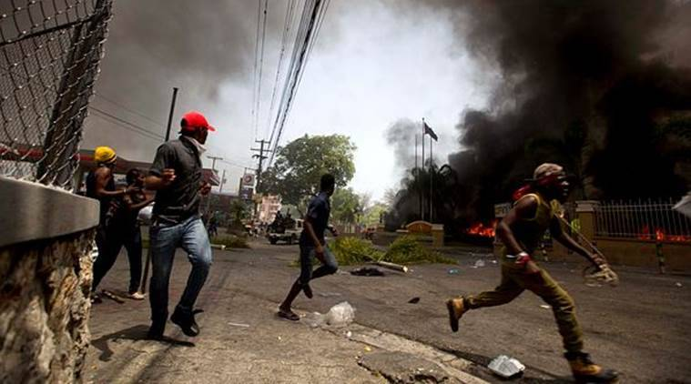 People run away to protect themselves from police officers while cars burn in the garage of the Royal Oasis hotel during a protest over the cost of fuel in Port-au-Prince, Haiti on Saturday. (AP)