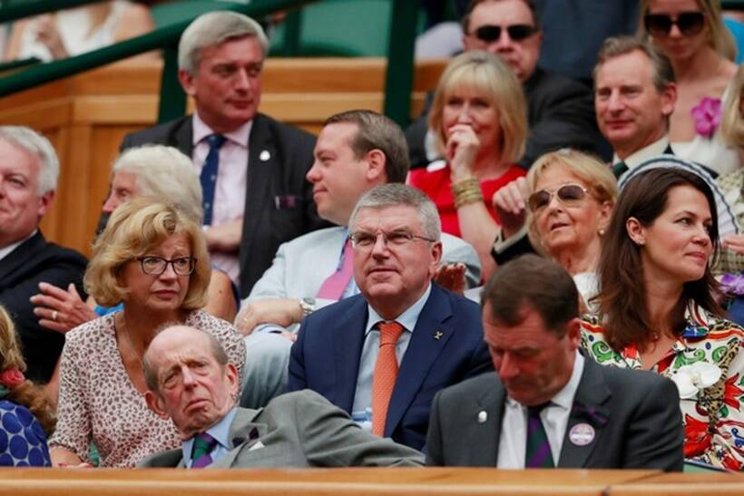 IOC President Thomas Bach watches Spain's Rafael Nadal continue his semi final match against Serbia's Novak Djokovic, which was suspended yesterday, after running late