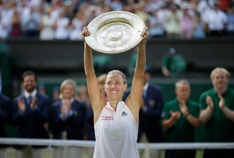 Germany's Angelique Kerber lifts the trophy after winning the women's singles final match against Serena Williams of the United States, at the Wimbledon Tennis Championships