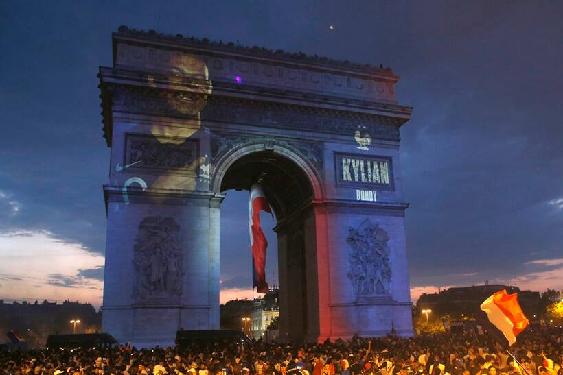 The name of French soccer player Kylian Mbappe is projected onto the Arc de Triomphe as soccer fans invade the Champs Elysees avenue after France won the soccer World Cup final match between France and Croatia