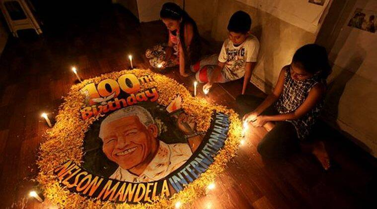 Children light candles beside a painting commemorating South African revolutionary Nelson Mandela's 100th birth anniversary at an art school in Mumbai on Wednesday. (Reuters)