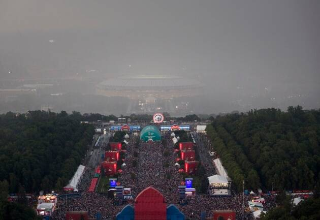 Soccer fans celebrate under a heavy rain in the fan zone near the Luzhniki stadium after the final match between France and Croatia at the 2018 soccer World Cup