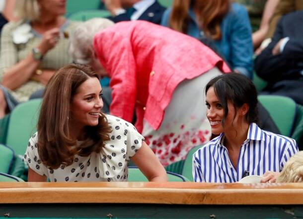 Kate, Duchess of Cambridge and Meghan, Duchess of Sussex, right, sit in the Royal Box on Centre Court at Wimbledon