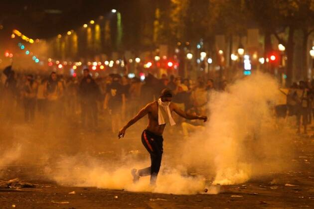 A man kicks a tear gas canister thrown by riot police during clashes on the Champs Champs Elysees avenue where soccer fans were celebrating France's World Cup victory over Croatia in Paris