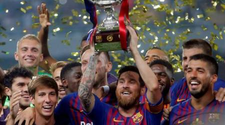Barcelona's Lionel Messi lifts the trophy as he celebrates winning the Spanish Super Cup with team mates