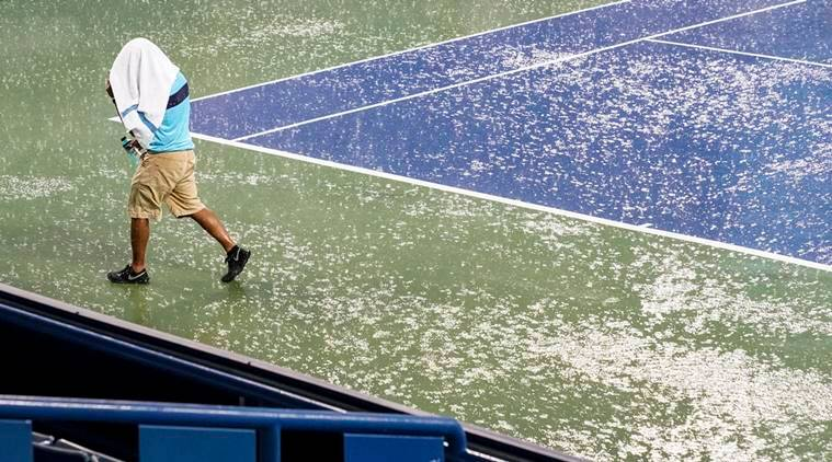 A court attendant moves toward shelter after play was suspended due to rain at the Western & Southern Open tennis tournament Thursday, Aug. 16, 2018, in Mason, Ohio