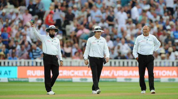 Umpires, from left, Aleem dar, Chris Gaffaney and Marais Erasmus walk in the field after play was suspended due to bad light conditions during the third day of the first test cricket match between England and India at Edgbaston in Birmingham, England