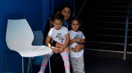 Mirka Federer (R), wife of Roger Federer of Switzerland, sits with their twin girls Myla Rose and Charlene Riva as they watch Federer arrive on court for his men's singles match against Teymuraz Gabashvili of Russia at the Australian Open 2014 tennis tournament in Melbourne