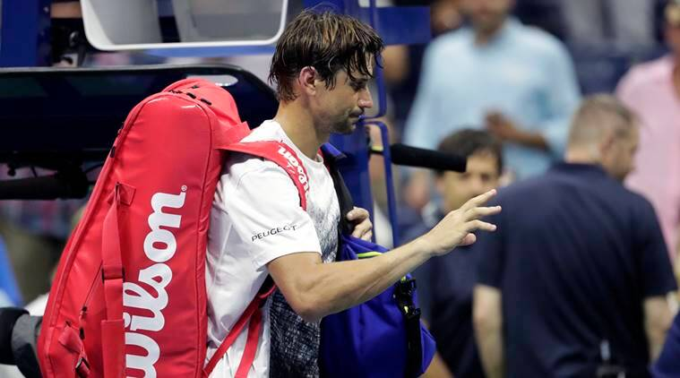 David Ferrer of Spain, leaves the court after retiring from his first-round match against Rafael Nadal, also of Spain, at the U.S. Open tennis tournament