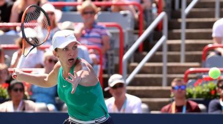 Simona Halep of Romania hits a shot against Ashleigh Barty of Australia during the Rogers Cup tennis tournament at Stade IGA in Montreal, Quebec